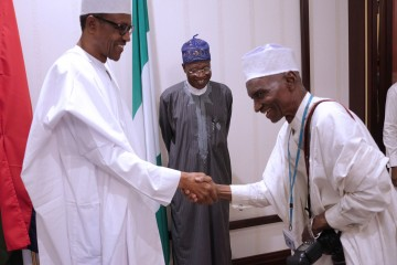 PRESIDENT BUHARI HOST STATEHOUSE PRESS CORP 1A&B.L-R; President Muhammadu Buhari in a handshake with the Oldest Photojournalist of Triumph Newspapers in the State House, Alhaji  Ladan Abubakar. With them is the Minister of Information, Alhaji Lai Mohammed as President hosts to a lunch State House Correspondents at the Presidential Villa in Abuja. PHOTO; SUNDAY AGHAEZE. MAY 30 2016