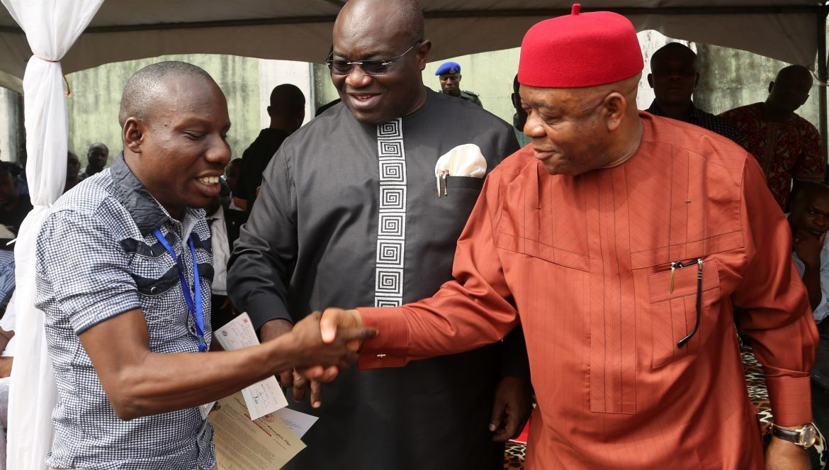 Sen. Theodore Orji  (right) in a handshake with one of the recipients of his Annual Scholarship Scheme for undergraduates from Abia Central Senatorial Zone, Mr.Mpama Frank Ifeanyi  (visually impaired) as Abia state Governor, Dr. Okezie Ikpeazu (middle) looks on at the ceremony in Umuahia.    Photo  Govt House Press