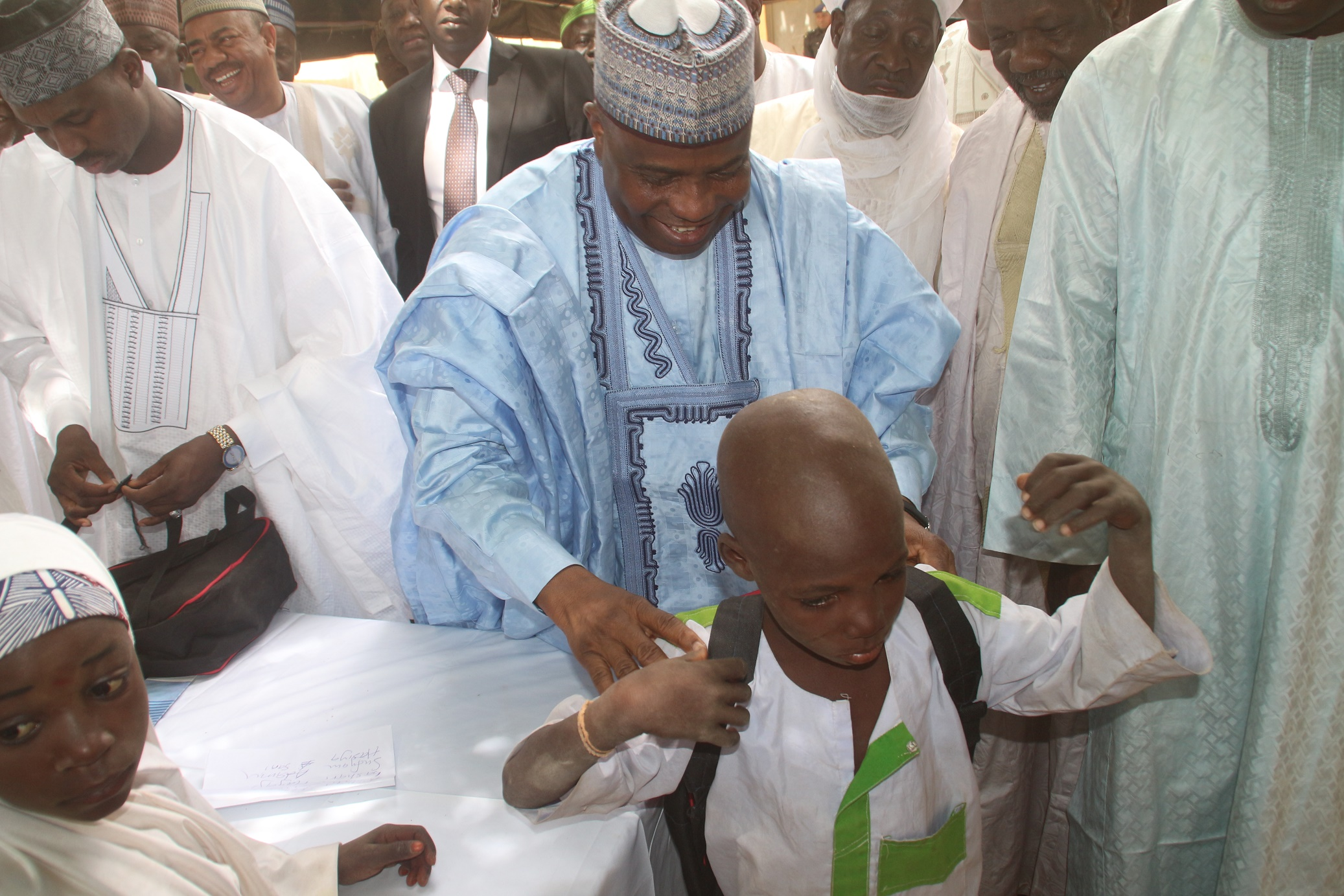 Enrollment 1: Governor Aminu Waziri Tambuwal presenting a school bag to young Safiyanu Adamu after he was enrolled in school for the first time, at the flag-off of Sokoto state school enrollment drive in Riji, Rabah LGA.