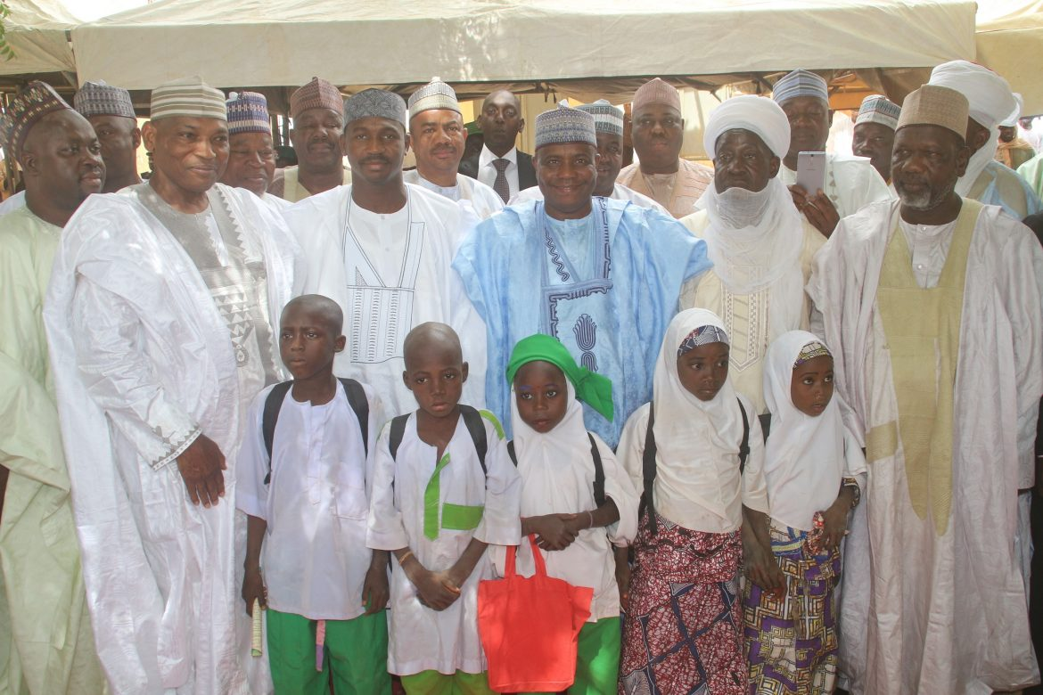 Enrollment 4: Governor Aminu Waziri Tambuwal in a group photograph with four of the newly-enrolled children and other government officials at the flag-off of Sokoto state school enrollment drive in Riji, Rabah LGA.